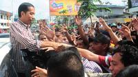 Menggunakan mobil kap terbuka, pria kurus yang karib disapa Jokowi itu menyapa para pedagang dan warga.