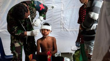 Petugas medis militer mengobati seorang anak laki-laki yang mengalami cedera akibat gempa Lombok di rumah sakit darurat di Kayangan, Rabu (8/8). BPBD Lombok Utara mencatat data sementara jumlah korban jiwa mencapai 347 orang. (AP/Fauzy Chaniago)