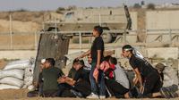 Warga Palestina berlindung dari pasukan Israel saat bentrok di Khan Yunis, Jalur Gaza, Jumat (13/9/2019). Kementerian Kesehatan Palestina mengatakan 55 warganya terluka oleh peluru tajam dan bom gas air mata pasukan Israel. (SAID KHATIB/AFP)