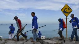 Peserta bersiap mengikuti kompetisi memancing di pantai Banda Aceh (24/11/2019). Para peserta ditempatkan di area sepanjang 2,5 kilometer, di sepanjang tanggul pesisir jalan yang menghubungi Gampong Jawa dan jembatan dekat Pelabuhan Ulee Lheue. (AFP Photo/Chaideer Mahyuddin)