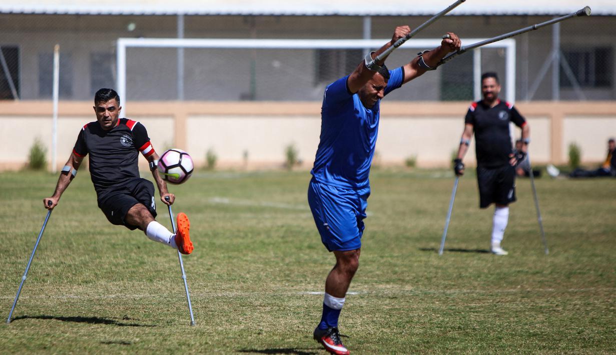 Seorang pemain klub Al-Jazeera (hitam) menendang bola dalam pertandingan final kejuaraan lokal sepak bola korban amputasi melawan Al-Abtal yang diselenggarakan oleh Komite Palang Merah Internasional (ICRC), di tengah pandemi COVID-19, di Kota Gaza, Palestina, (18/3/2021). (AFP/Mohammed Abed)