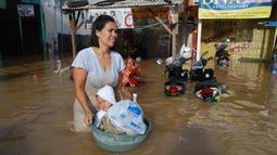 Seorang ibu membawa anaknya menggunakan ember untuk melintasi banjir di kabupaten Bandung, Jawa Barat, Minggu (13/3). Kawasan Bandung Selatan kembali dilanda banjir akibat luapan Sungai Citarum dan membuat ribuan orang mengungsi. (Timur Matahari/AFP)