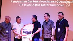Direktur PT Isuzu Astra Motor Indonesia (IAMI) Ary A. Mariano (kedua kiri) menyerahkan bantuan kendaraan operasional kepada Yayasan Amaliah Astra Riza Deliansyah (tengah) pada puncak Astra Gema Islami (AGI) 2019 di Jakarta, Jumat (12/7/2019). (Liputan6.com/HO/Ilham)