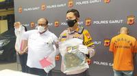 Kepolres Garut AKBP Wirdhanto Hadicaksono, menunjukan tas dan barang bukti lainnya yang digunakan tersangka dalam aksi laporan palsu korban begal motor, dalam rilis perkara di Mapolres Garut, Senin (11/10/2021). (Liputan6.com/Jayadi Supriadin)
