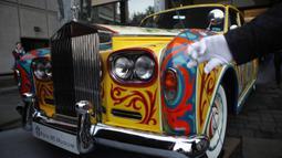 Rolls-Royce limusin touring Phantom V milik John Lennon terlihat Museum Royal BC di Victoria, British Columbia (27/1/2020). Warna asli mobil ini adalah hitam sebelum dicat ulang dengan gaya Romany yang berwarna-warni. (Chad Hipolito/The Canadian Press via AP)