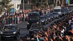 Ratusan warga menyambut iringan mobil jenazah Presiden Uzbekistan, Islam Karimov di Tashkent, Uzbekistan, (3/9).  Islam Karimov mengembuskan napas terakhir setelah enam hari menjalani perawatan intensif di rumah sakit. (REUTERS/Muhammadsharif Mamatkulov)