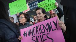 Sejumlah orang menggelar aksi protes kepada United Airlines di Bandara Internasional O'Hare, Chicago, AS, Selasa (11/4). Demonstran mengecam tindakan polisi yang mengeluarkan penumpang tidak manusiawi). (Scott Olson / Getty Images / AFP)