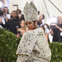 Penyanyi Rihanna berpose untuk fofotgrafer setibanya pada pagelaran Met Gala 2018 di Museum Seni Metropolitan New York, Senin (7/5). Menyempurnakan gayanya, aksesori di kepalanya yang menyerupai mitre atau mitra. (Evan Agostini/Invision/AP)