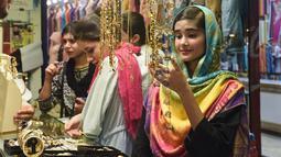 Seorang perempuan Pakistan memilih pernak-pernik di sebuah pasar di Lahore, Selasa (12/6). Umat muslim di berbagai penjuru dunia sedang mempersiapkan untuk merayakan Idul Fitri, yang menandai berakhirnya bulan suci Ramadan. (AFP/ARIF ALI)
