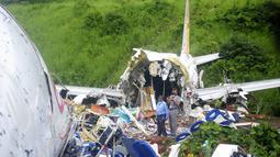 Petugas berdiri di atas puing-puing pesawat Air India Express yang tergelincir dari landasan pacu saat mendarat di Kozhikode, negara bagian Kerala, India, Sabtu, (8/8/2020). Pesawat Air India Express dengan 190 orang di dalamnya jatuh di sebuah bandara di negara bagian selatan Kerala. (AP Photo/C.K.