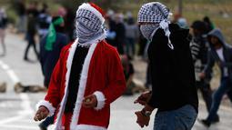Seorang demonstran Palestina mengenakan kostum Santa Claus bersiap melempar batu ke arah pasukan keamanan Israel saat terjadi bentrokan di pos pemeriksaan Atarot di pinggiran utara Yerusalem (19/12). (AFP Photo/Abbas Momani)