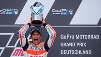 Marc Marquez dengan trofi MotoGP Jerman, Minggu (17/7/2016). Ini adalah kemenangan ke-7 beruntun Marquez dari 7 kali pole di Sirkuit Sachsenring, Jerman. (AFP/Robert Michael)
