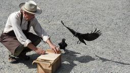 Burung  gagak dilatih memungut sampah di taman Puy du Fou, Prancis barat, Selasa (14/8). Burung gagak itu dilatih bukan hanya untuk membersihkan taman bermain tapi juga mengedukasi kepada pengunjung supaya menjaga kebersihan. (AFP/SEBASTIEN SALOM GOMIS)