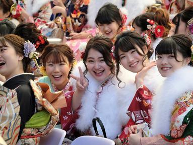 Sejumlah gadis Jepang mengenakan kimono saat menghadiri upacara Coming of Age Day atau Hari Kedewasaan di Tokyo Disneyland, di Urayasu, Senin (13/1/2020). Hari Kedewasaan adalah hari libur umum Jepang yang diadakan setiap hari Senin, minggu kedua di bulan Januari tiap tahunnya. (Kazuhiro NOGI/AFP)