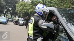 Petugas melakukan tilang di tempat ke salah satu pelanggar aturan pembatasan kendaraan sistem ganjil genap di kawasan Sudirman, Jakarta, Selasa (30/8). Hari ini resmi diberlakukan denda bagi pelanggar aturan sistem ganjil genap (Liputan6.com/Yoppy Renato)