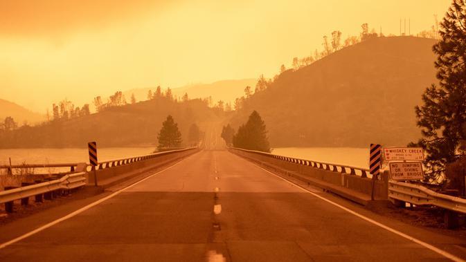 Langit berubah menjadi oranye gelap saat asap memenuhi wilayah kebakaran hutan yang dijuluki Carr Fire di Whiskeytown, California, Jumat (28/7). Bencana yang melanda California akibat gelombang panas di negara bagian itu. (JOSH EDELSON/AFP)