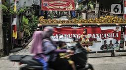Pengendara sepeda motor melintas di depan salah satu pintu masuk Kampung Bali saat perayaan Hari Nyepi, Harapan Jaya, Bekasi, Jawa Barat, Minggu (14/3/2021). Toleransi beragama untuk saling menghormati di kampung ini sangat terjaga. (merdeka.com/Iqbal S. Nugroho)