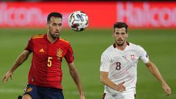 Gelandang Spanyol, Sergio Busquets (kiri) mengontrol bola dari kawalan pemain Swiss, Remo Freuler  pada pertandingan  UEFA Nations League di Alfredo Di Stefano, Madrid, Spanyol (10/10/2020). Madrid menang tipis atas Swiss 1-0. (AP Photo/Manu Fernandez)