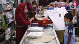 Pedagang melayani pembeli seragam sekolah baru di salah satu toko di Tangerang, Banten, Selasa (2/6/2020). Menjelang tahun ajaran baru, sejumlah pedagang di tempat tersebut mengeluh karena omzet penjualan seragam sekolah menurun drastis akibat pandemi COVID-19. (Liputan6.com/Angga Yuniar)