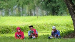 Anggota keluarga membaca yasin di sebuah kuburan massal korban tsunami Aceh di Aceh, Senin (26/12). Warga memperingati 12 tahun pasca gempa dan tsunami dengan berziarah ke makam-makam massal korban gempa dan tsunami. (CHAIDEER MAHYUDDIN/AFP)