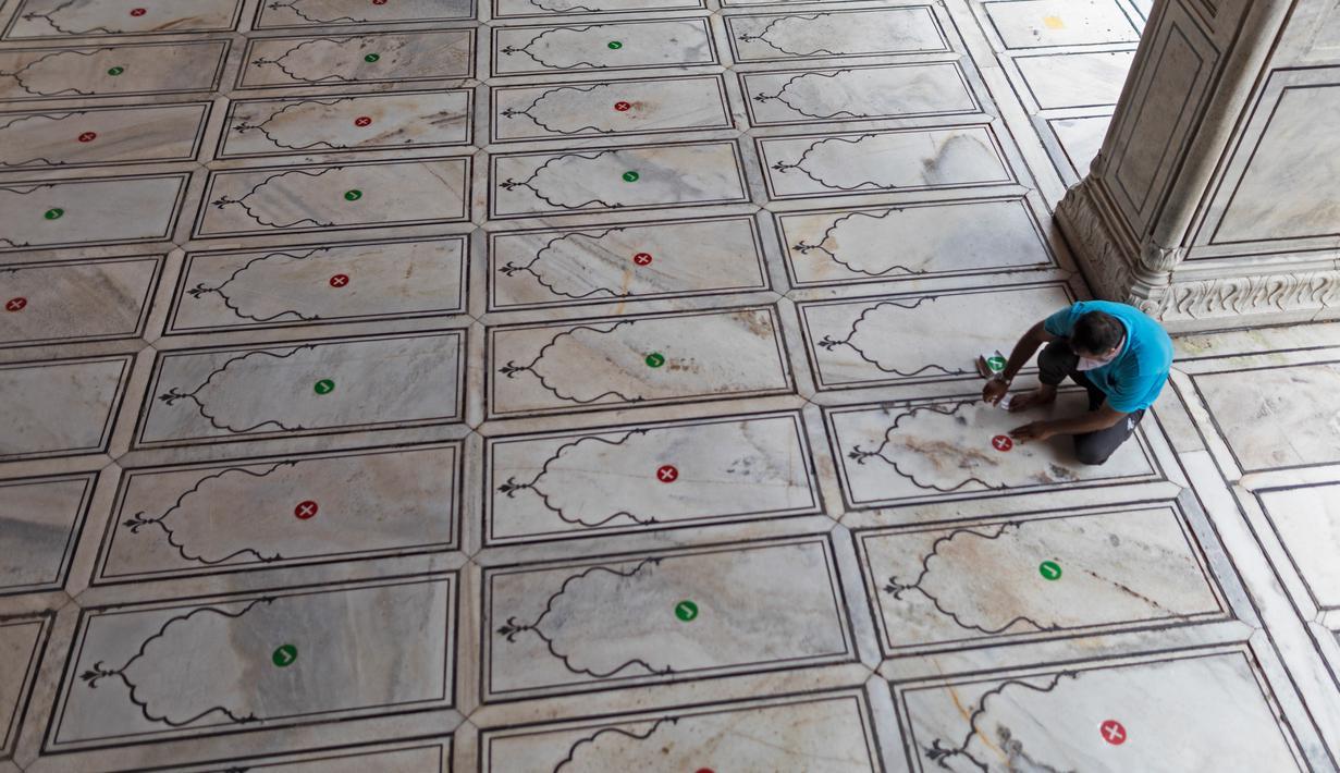 Pengurus menempelkan stiker di lantai bagi jemaah agar menjaga jarak selama salat ketika Masjid Jama dibuka kembali setelah pelonggaran lockdown di kawasan Kota Tua Delhi, Selasa (7/7/2020). India pada 6 Juli menjadi negara dengan jumlah virus corona tertinggi ketiga di dunia. (XAVIER GALIANA/AFP)