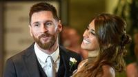 Ekspresi Lionel Messi  bersama istrinya Antonella Roccuzzo  usai melangsungkan pernikahan di Rosario, provinsi Santa Fe, Argentina (30/6). Dalam acara itu turut hadir Luis Suarez, Angel di Maria, Xavi Hernandez dan lainnya. (AFP Photo/Eitan Abramovich)