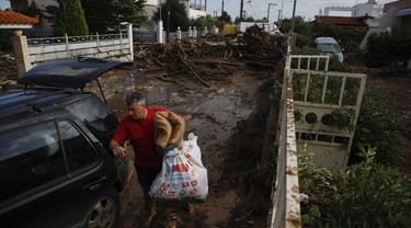 Seorang pria membawa barang miliknya dari rumahnya yang rusak ke mobilnya setelah badai di desa Kineta, Athena (25/11/2019). Pihak berwenang di Yunani mengatakan dua orang telah tewas dan ratusan lainnya luka-luka. (AP Photo/Petros Giannakouris)