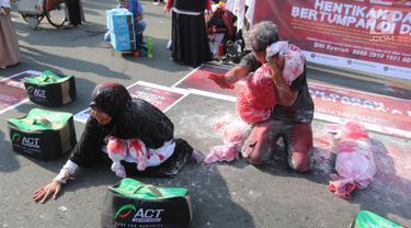 Dua relawan dari Aksi Cepat Tanggap (ACT) saat melakukan teatrikal tentang penderita rakyat Suriah yang menjadi korban peperangan di CFD Bundaran HI, Jakarta, Minggu (15/7). (Liputan6.com/Arya Manggala)