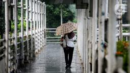 Pejalan kaki berjalan saat hujan lebat di JPO kawasan Jalan Sudirman, Jakarta, Selasa (29/6/2021). Hujan dan hawa dingin di musim kemarau karena ada gangguan atmosfer 'Indian Ocean dipole mode' yang masih negatif serta diperkirakan terjadi hingga akhir Juni. (Liputan6.com/Faizal Fanani)