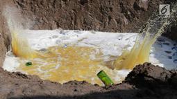 Pemusnahan minuman keras (miras) di Polres Gorontalo, Gorontalo, Jumat (4/1). Miras tersebut merupakan hasil sitaan Polres Gorontalo dalam beberapa bulan terakhir. (Liputan6.com/Arfandi Ibrahim)