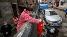 Seorang penduduk menerima sekantong makanan di atas tembok di Wuhan di provinsi Hubei tengah China (3/3/2020). Wuhan merupakan kota di China yang menjadi awal mula wabah virus corona. (AFP/STR)