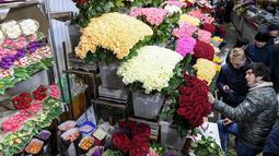Pedagang bunga melayani pembeli jelang Hari Perempuan Internasional di pasar bunga di Moskow, Rusia (5/3). Hari Perempuan Internasional secara resmi dijadikan sebagai hari libur nasional di Soviet Rusia pada tahun 1917. (AFP Photo/Kirill Kudryavtsev)