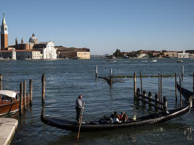Seorang gondolier mendayung gondola di dekat gereja Santa Maria della Salute di Venesia pada 20 Mei 2021.  Turis kembali berdatangan menikmati keindahan Venesia, yang sering dijuluki kota paling romantis di dunia, setelah Italia menghapus kewajiban karantina bagi pendatang. (Marco Bertorello/AFP)