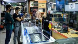 Calon pembeli melihat-lihat produk laptop di pusat elektronik Harco Mangga Dua, Jakarta, Selasa (9/3/2021). Perusahaan riset pasar Canalys memprediksi angka penjualan PC dan laptop kembali di angka 300 juta unit pada 2020 atau naik 15 persen dibandingkan 2019. (merdeka.com/Imam Buhori)