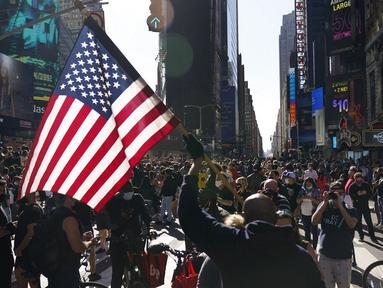 Orang-orang merayakan kemenangan Joe Biden dalam Pilpres AS 2020 di Times Square, New York, Amerika Serikat, Sabtu (7/11/2020). Calon presiden dari Partai Demokrat tersebut keluar sebagai pemenang dan akan menjadi presiden AS ke-46. (AP Photo/Seth Wenig)