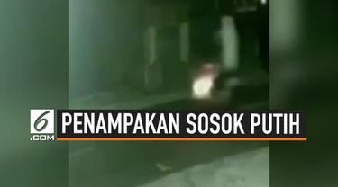 Beredar heboh di media sosial, video penampakan sosok putih berdiri diatas motor. Penampakan ini tertangkap kamera CCTV.