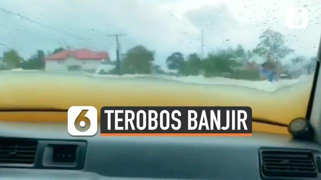 Seorang pengendara mobil lakukan aksi nekat dengan terobos banjir yang hampir menutupi mobilnya. Alhasil, air banjir pun masuk ke dalam mobilnya.