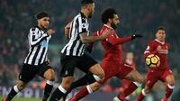 Gelandang Liverpool Mohamed Salah membawa bola berusaha melewati bek Newcastle DeAndre Yedlin saat pertandingan Liga Inggris di Anfield, Liverpool (3/3). Salah berhasil menyumbang satu gol untuk Liverpool pada menit ke-40. (AFP Photo/Lindsey Parnaby)