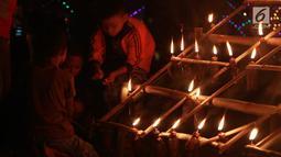 Anak-anak menyalakan lampu minyak saat perayaan tumbilotohe atau penyalaan berjuta lampu minyak di akhir Ramadan di Kota Gorontalo, Jumat (31/5/2019). Ribuan warga tumpah ruah ke sejumlah tempat untuk menyaksikan indahnya hiasan lampu temaram tersebut. (Liputan6.com/Arfandi Ibrahim)