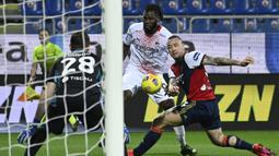 Gelandang AC Milan, Franck Kessie (tengah) melepaskan tendangan dibayangi gelandang Cagliari, Radja Nainggolan dalam laga lanjutan Liga Italia 2020/21 pekan ke-18 di Sardegna Arena, Senin (18/1/2021). AC Milan menang 2-0 atas Cagliari. (AFP/Alberto Pizzoli)