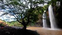 Sejumlah wisatawan menikmati curug Sodong Kembar di kawasan Ciletuh Geopark, Sukabumi, Sabtu (23/6). Tempat ini kian populer karena keindahan alamnya dan batuan alamnya yang dihadirkan di setiap obyek wisata di Geopark Ciletuh. (Merdeka.com/Arie Basuki)