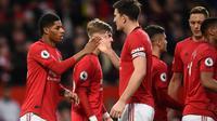 Striker Manchester United, Marcus Rashford (kiri) berselebrasi dengan rekan-rekannya usai mencetak gol ke gawang Norwich City pada pertandingan lanjutan Liga Inggris di Old Trafford (11/1/2020). Rashford mencetak dua gol dan mangantar MU menang telak 4-0 atas Norwich. (AFP/Oli Scarff)