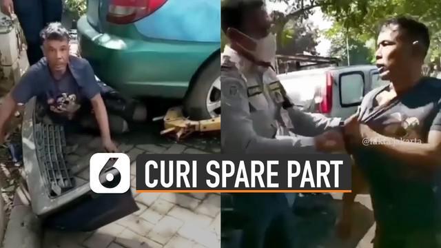 Aksi nekat dilakukan oleh seorang pria mencuri spare part mobil yang sedang terparkir.