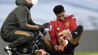 Striker Manchester United atau MU Marcus Rashford melepas sepatunya setelah cedera saat melawan Manchester City dalam lanjutan Liga Inggris di Etihad Stadium, Minggu (7/3/2021). (Peter Powell / Pool via AP)