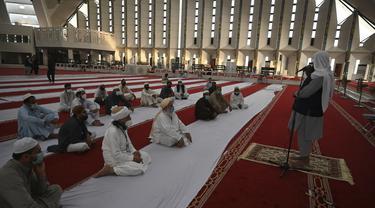 Umat Muslim mendengarkan Imam (kanan) di Masjid Agung Faisal di awal Itikaf, di sebuah masjid untuk pria selama bulan suci Ramadhan di Islamabad (3/5/2021). Umat Muslim melakukan Itikaf 10 hari terakhir bulan Ramadhan, dalam rangka meraih malam kemuliaan atau Lailatul Qadar. (AFP/Aamir Qureshi)