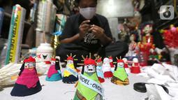 Pekerja membuat ondel-ondel dari shuttlecock atau kok bekas di perkampungan Budaya Betawi, Srengseng Sawah, Jakarta, Sabtu (8/8/2020). Selama masa pandemi Covid-19 pesanan dan penyewaan ondel-ondel sepi tanpa ada pemasukan. (Liputan6.com/Fery Pradolo)