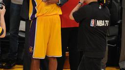 Pemain Los Angeles Lakers, Kobe Bryant memeluk pelatihnya usai pertandingan antara Lakers melawan Utah Jazz di Staples Center, AS, (13/4).Pebasket NBA tersebut menyatakan pensiun dari NBA setelah 20 tahun berkarir. (Gary A. Vasquez-USA TODAY Sports)