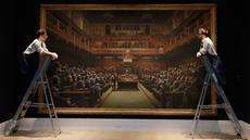 Petugas mengamati lukisan seniman jalanan Banksy yang dipajang di ruang lelang Sotheby, London, Jumat (27/9/2019). Lukisan Banksy 'Devolved Parliament' itu bakal dilelang yang diperkirakan bernilai 1,5-2 juta poundsterling (Rp25-35,1 miliar) pada Oktober mendatang. (AP/Kirsty Wigglesworth)