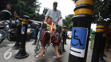 Lansia berkursi roda melintasi Portal S Ramah Disabilitas di trotoar RSCM, Jakarta, Jumat (26/8). Selain ramah disabilitas dan Lansia, portal tersebut juga berfungsi untuk mencegah sepeda motor masuk ke jalur trotoar. (Liputan6.com/Immanuel Antonius)
