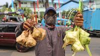 Pedagang menunjukkan kulit ketupat dan ketupat siap hidang di kawasan Cibubur, Jakarta, Rabu (30/7/2020). Pedagang musiman menjelang Idul Adha tersebut menjual kulit ketupat dengan harga Rp 10 ribu, sedangkan ketupat yang siap untuk dihidangkan seharga Rp 30 ribu. (Liputan6.com/Herman Zakharia)